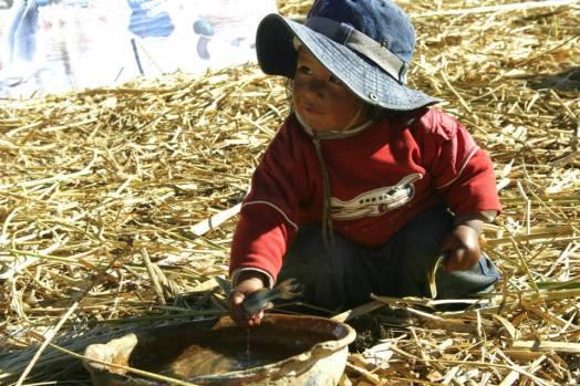 Titikakasee: kleiner Junge spielt mit Fischen