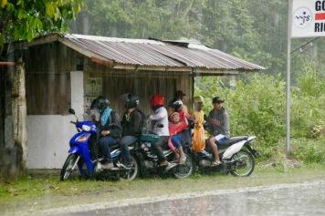 Einheimische warten auf das Ende des Regenguss'