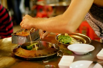 Satayspieße in einer Garküche selbst zubereiten