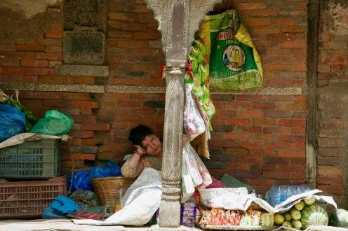 Eine Verkäuferin kurz vorm Nickerchen in Kathmandu