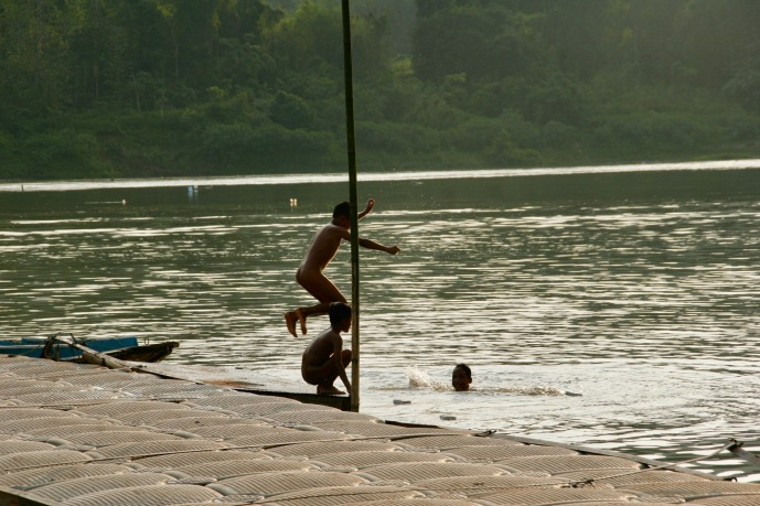 Kinder spielen und schwimmen im Mekong