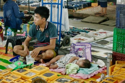 Papa mit schlafendem Kind auf dem Nachtmarkt