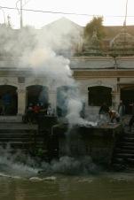 Verbleibende Asche wird in den heiligen Bagmati Fluss gefegt