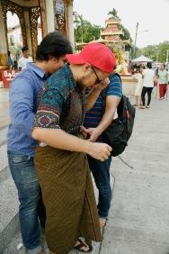 Zwei Jungs helfen Alex beim Anziehen des Longyi