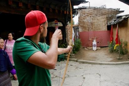 Alex probiert sich im Bogenschießen im Simply Bhutan