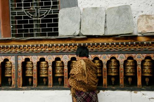 Frau dreht die Gebetsrollen beim Changangkha Kloster
